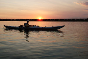 Photo of a kayaker paddling in the sunset with a train off in the distance