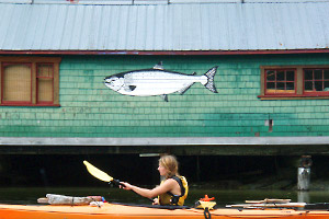 Photo of a woman paddling her kayak in front of a marine building with a picture of a salmon on it
