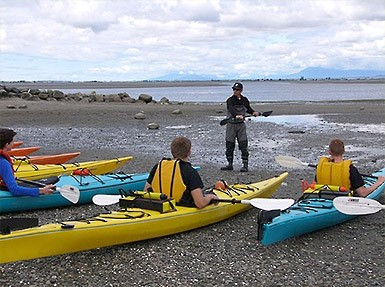 Photo of a group of kayakers receiving instruction